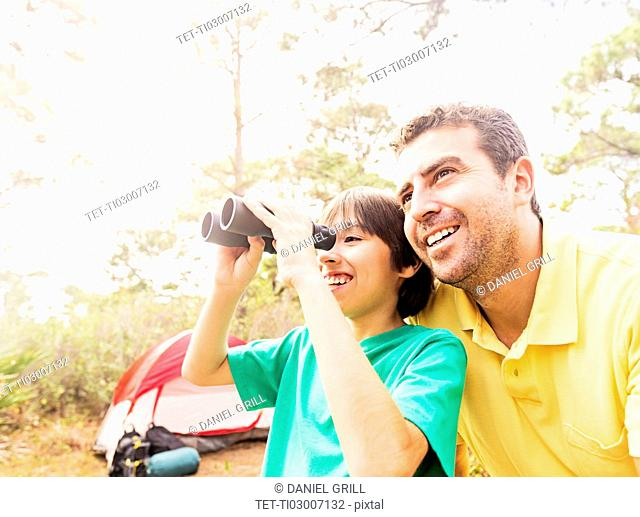 Father and son (12-13) using binoculars