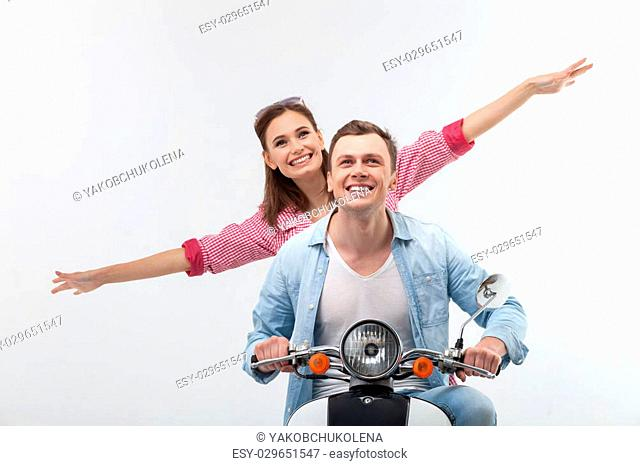I feel this freedom. Cheerful young loving couple is enjoying their journey on scooter. The woman is stretching her arms sideways and smiling