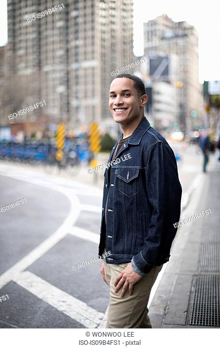 Portrait of young man standing in street, Manhattan, New York, USA