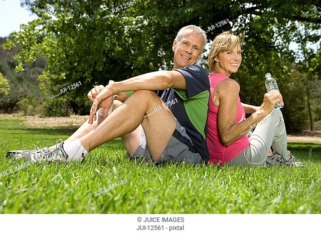 Mature couple sitting back to back in park, smiling, portrait, low angle view