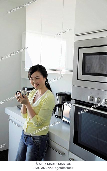 Woman leaning against kitchen counter