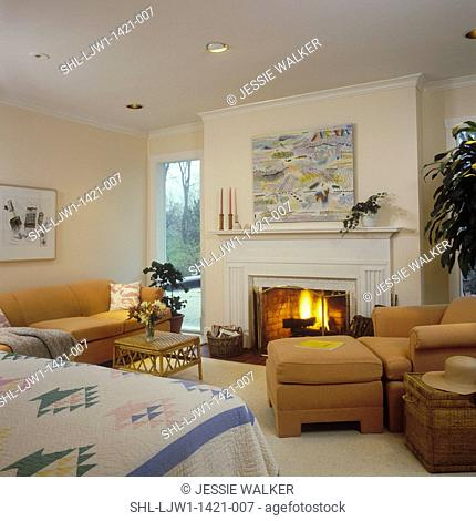 BEDROOM - Bedroom sitting area, fireplace, sofa, chair and ottoman, edge of bed with pastel quilt, pale walls, traditional