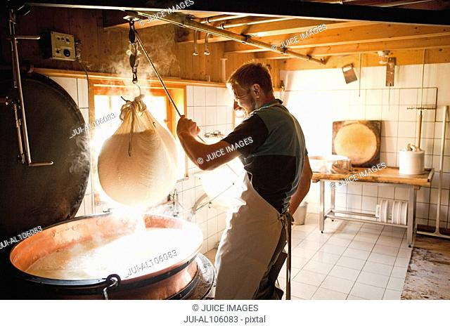 Mid adult man making cheese in Oberstaufen, Allgau, Bavaria, Germany