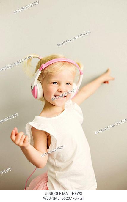 Portrait of blond little girl with headphones dancing