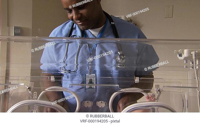Male hospital worker caressing newborn in incubator