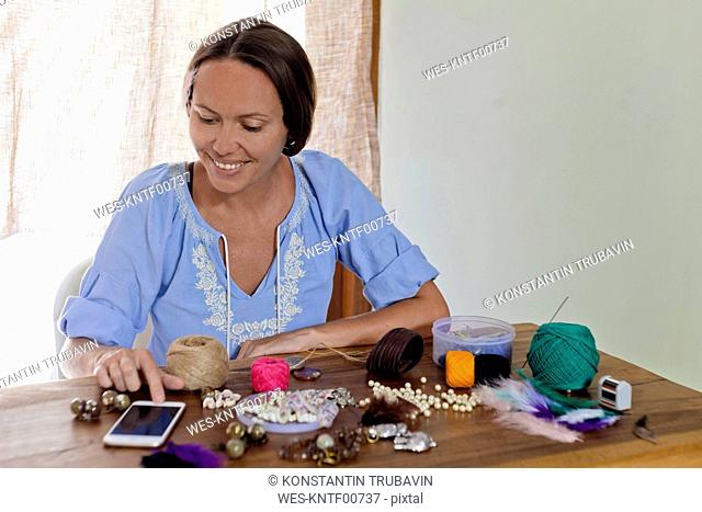 Woman using cell phone and doing handicraft on wooden table
