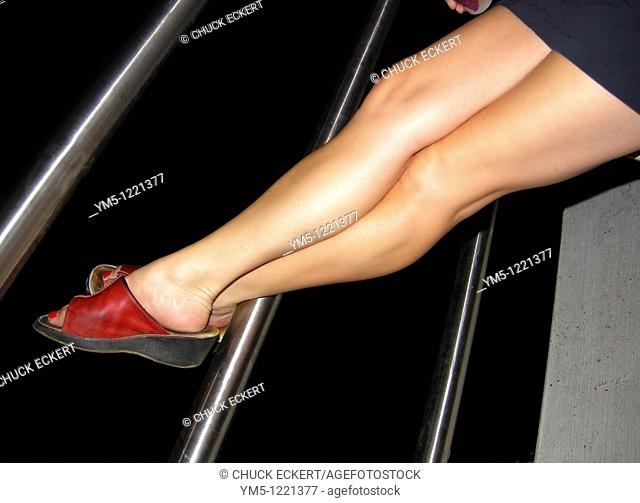 Woman's Legs Resting on Railing