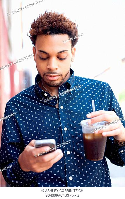 Young man looking at cellphone with drink in hand