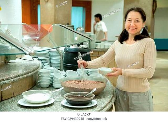 Woman takes chocolate cereals on the buffet table