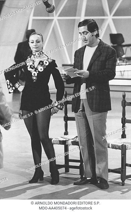 Raffaella Carrà and Corrado in Canzonissima. Italian TV host, actress, singer and showgirl Raffaella Carrà (Raffaella Maria Roberta Pelloni) listening to...