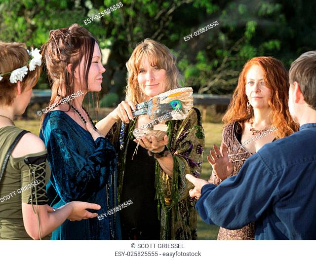 Group of Wicca men and women using feather and incense