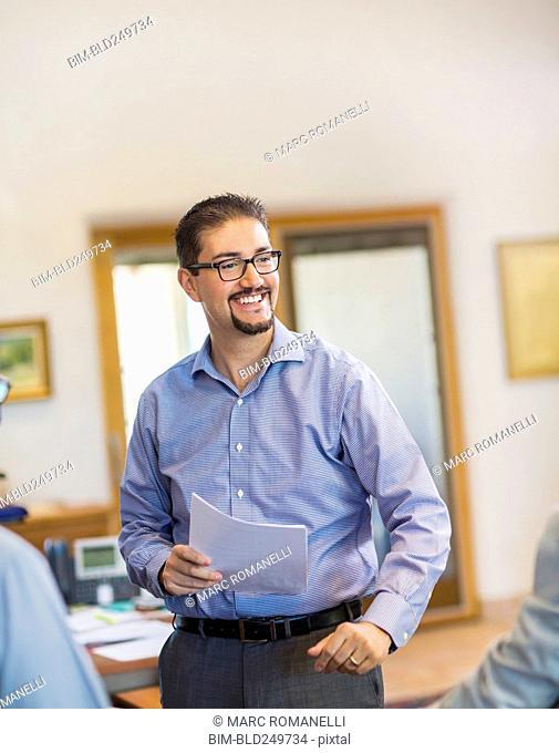 Smiling Hispanic businessman holding paperwork in office