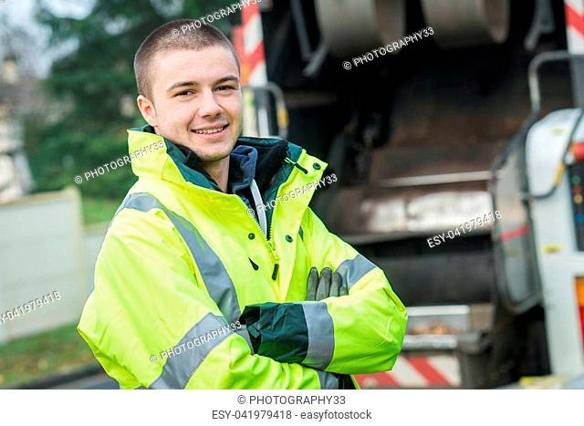 young garbage collector standing near his truck