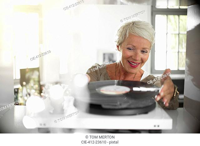 Older woman playing vinyl record on turntable