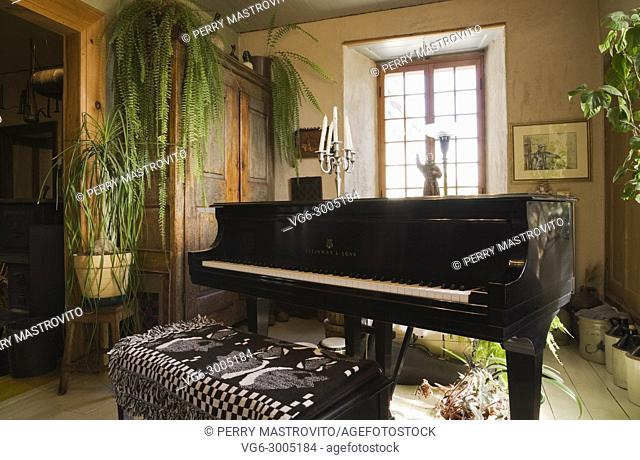 Steinway piano and wooden armoire in the music room inside an old Canadiana (1840s) fieldstone cottage style residential house, Quebec, Canada