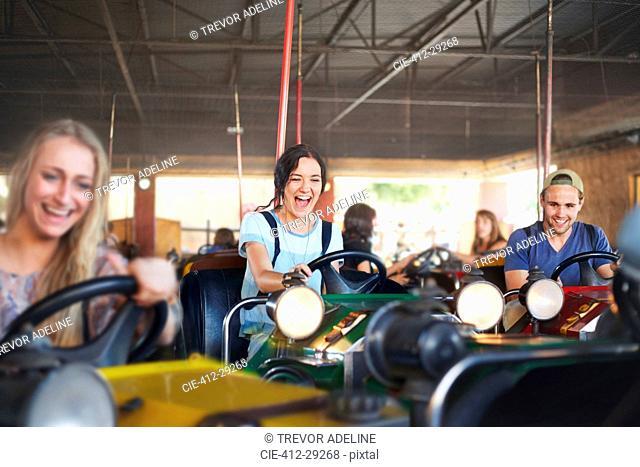 Enthusiastic friends riding bumper cars at amusement park