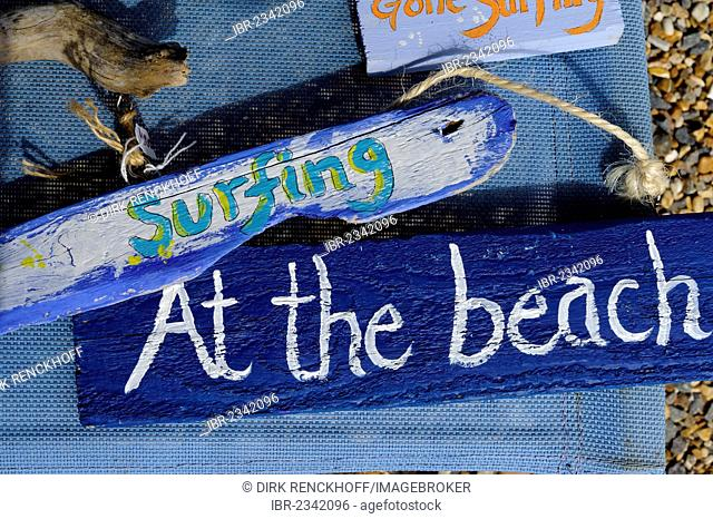 Signs, surfing, At the beach, Fish'n Beads store on the beach at St. Brelade's Bay, Jersey, Channel Islands
