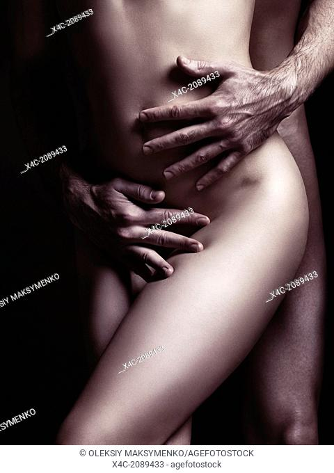 Sensual couple artistic nude closeup photo. Man hands embracing naked woman body. Black and white sepia toned