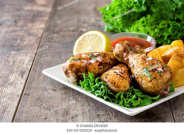 Roast chicken drumsticks and chips on wooden table