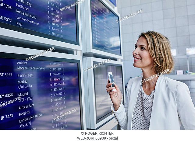 Businesswoman with cell phone at timetable at the airport