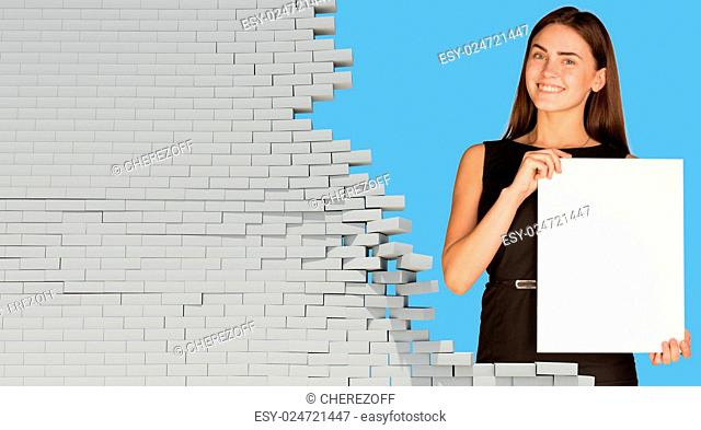 Beautiful businesswoman holding blank paper sheet. Dilapidated brick wall as backdrop. Business concept