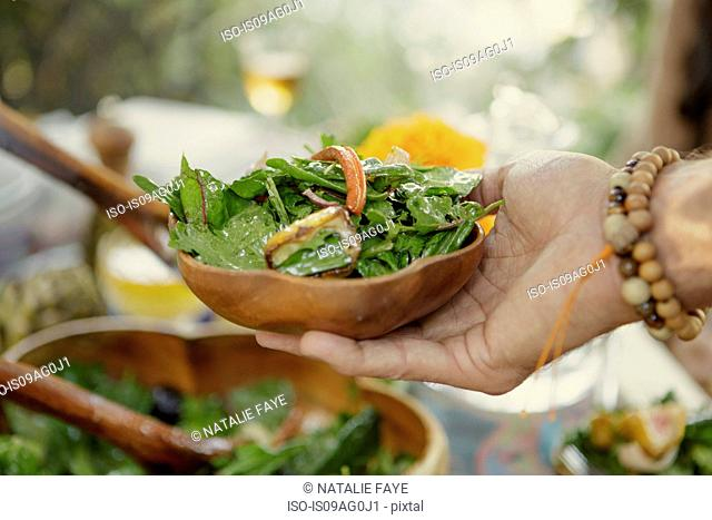 Close up of hand holding salad bowl at garden party