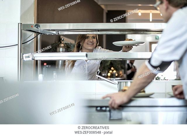 Waiter picking up food from the kitchen