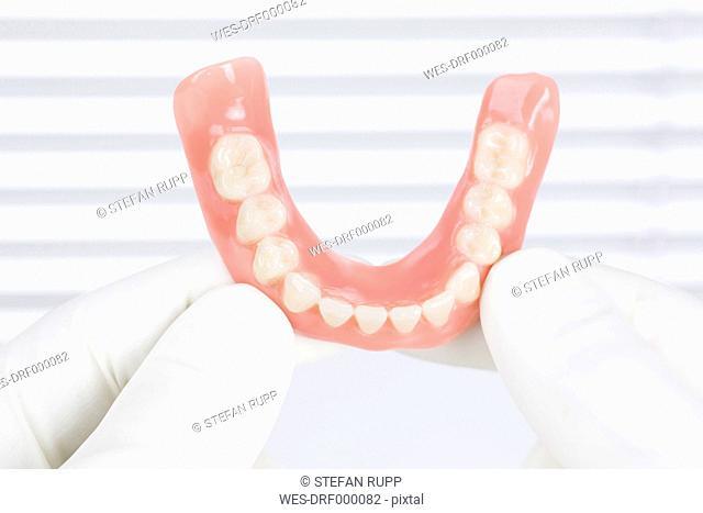 Germany, Freiburg, Dentist holding dentures, close up