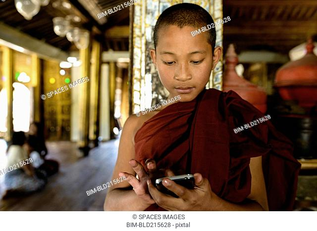 Asian monk-in-training using cell phone indoors