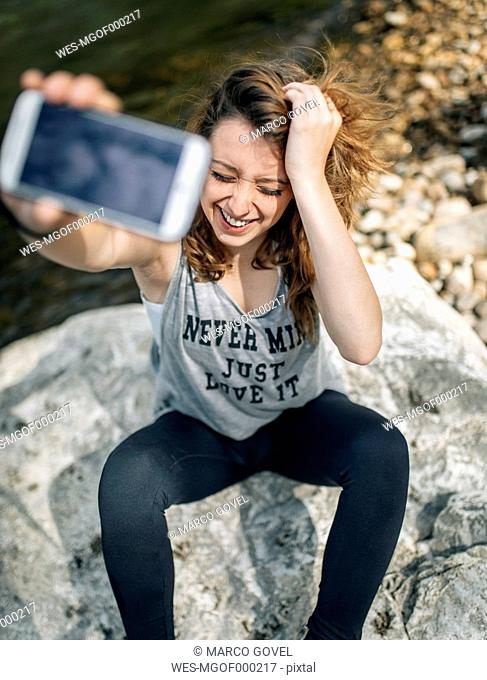 Portrait of a laughing young woman sitting on a rock taking selfie with a smartphone