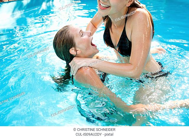 Two teenage girls jumping in swimming pool