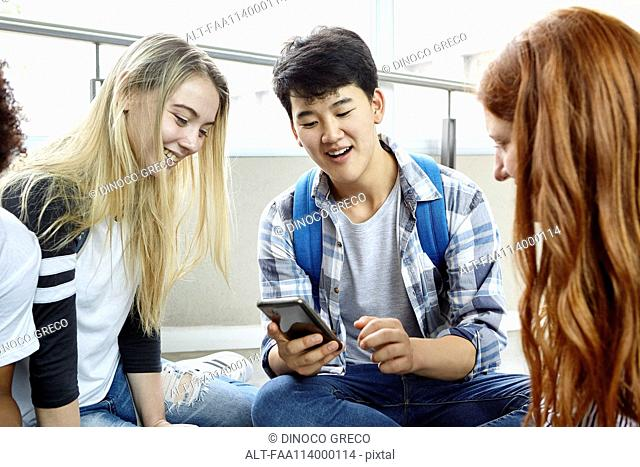 Student showing smart phone to classmates