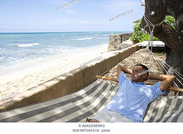 Mature man lying on hammock