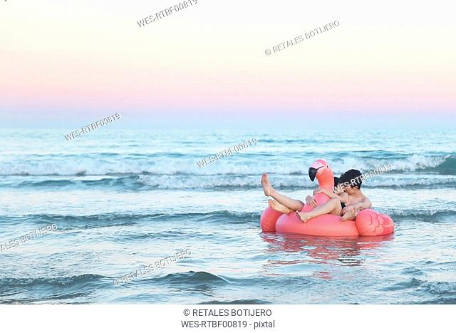 Couple in love floating with inflatable pink flamingo on the sea at sunset