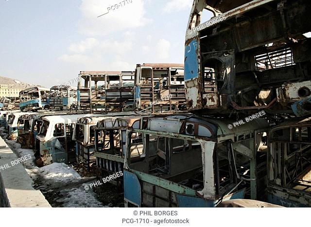 The effect of the conflict in Afghanistan. Stacked ruined buses and trams from the transport system, in a scrap yard