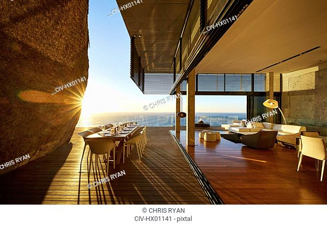 Sun setting behind modern luxury patio dining table with ocean view