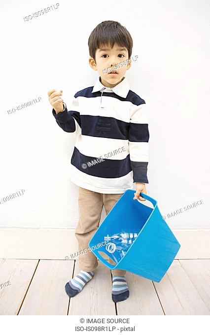 A boy holding a recycling bin