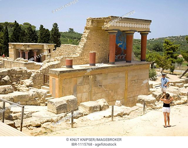 Tourists visiting and taking pictures of the arcade of columns at the northern entrance of the palace on the grounds of the Minoan excavation of Knossos