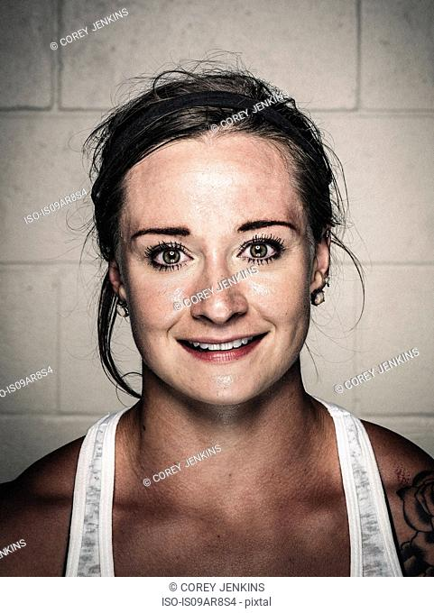 Portrait of sweaty smiling young woman after workout