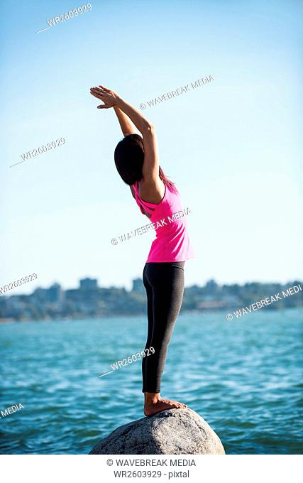 Woman performing yoga on rock