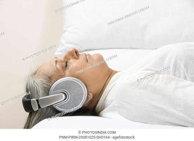 Woman listening to music on the bed
