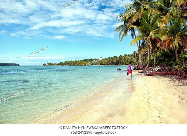 young male tourist walking barefoot on sandy beach, Colon Island, Bocas del Toro Archipelago, Bocas del Toro Province, Panama, Central America, America