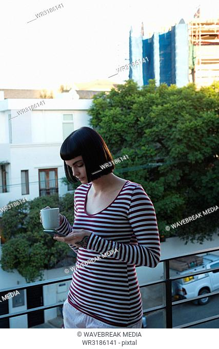 Woman having coffee while using mobile phone in the balcony