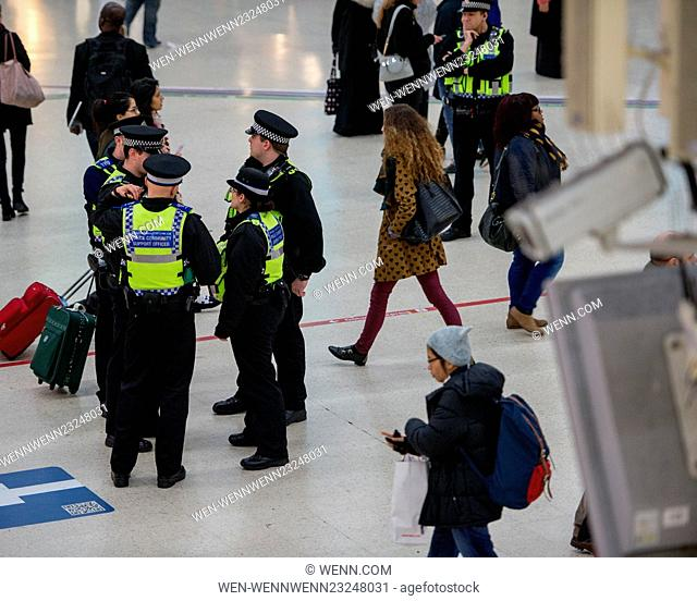A CCTV camera watches from above as officers guard Victoria Station. The Metropolitan Police are posting more officers in Underground Stations following the...