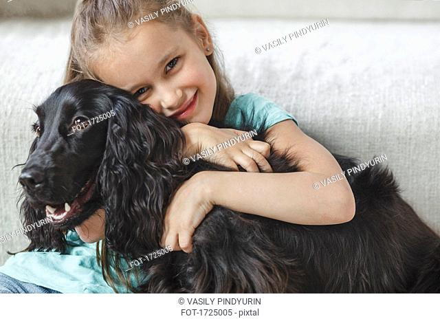 Portrait of smiling girl embracing dog at home