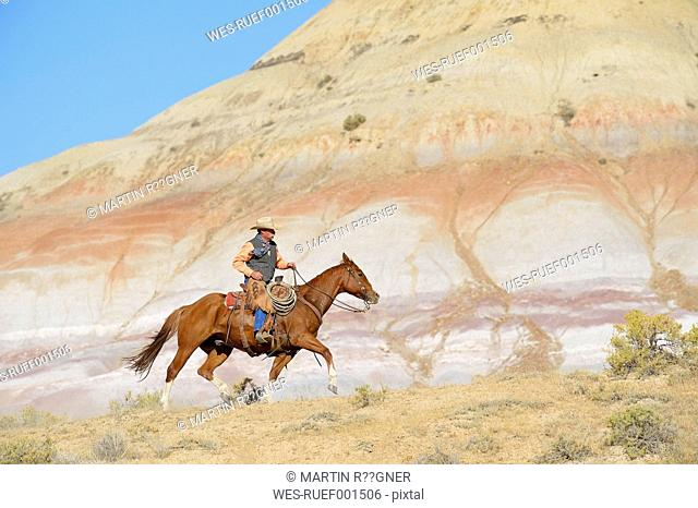 USA, Wyoming, cowboy riding in badlands