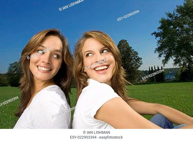 Two teenage friends sitting back to back