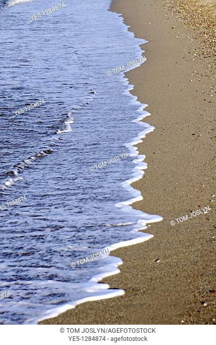 Waves washing up on sandy beach, Rhodes, Greece