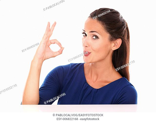 Cute lady in blue t-shirt making an ok sign while looking at you in white background