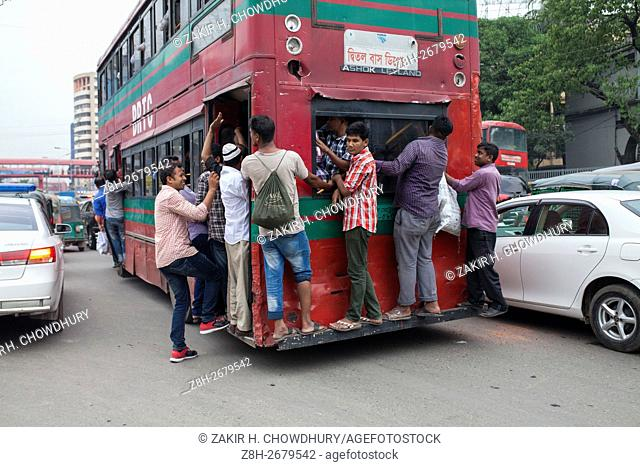 DHAKA, BANGLADESH - JUNE 12 : People hang on to an overcrowded bus to travel home, as others wait for transport ahead of Iftar